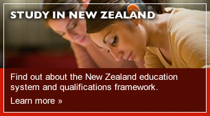 Image of two students leaning over some work with a link to Study in New Zealand Study in New Zealand